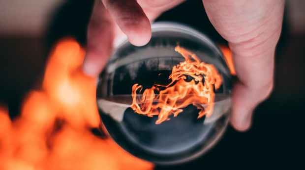person holding clear glass ball with flame